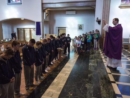 The Rev. Michael Warden blesses the Roncalli boys team