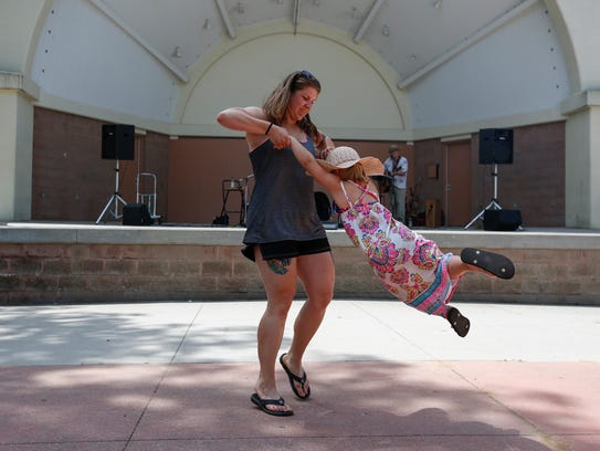 Jenna Brandt swings her daughter Audrey, 4, while the