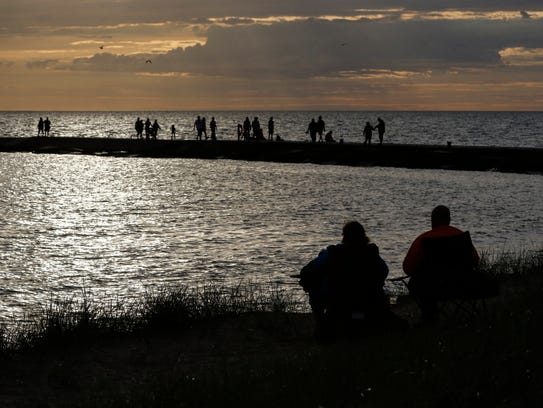 A couple watches the sunset at Stearns Park Beach as