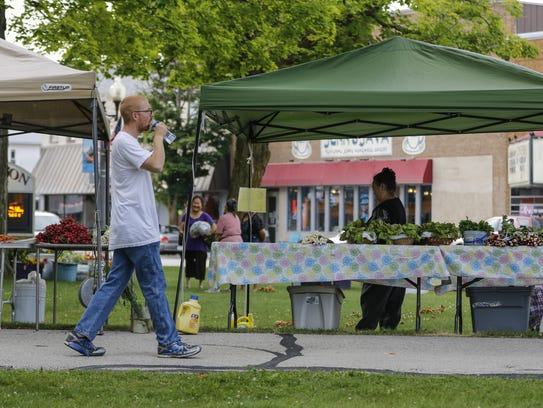 A man walks through the Tuesday farmers' market at Washington Park July 11, 2017.