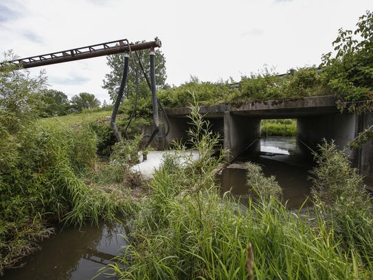 A truck pumps manure out of Pine Creek after runoff