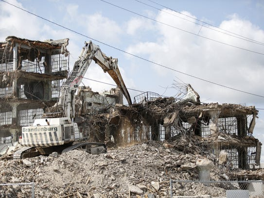 An excavator removes debris from the Mirro building
