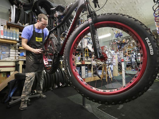 Ezra Schoonover repairs a fat bike at Cranked Bike