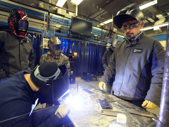 Welding instructor Luis Bolanos watches students weld