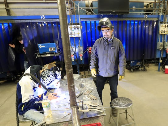 Welding instructor Luis Bolanos observes a student's
