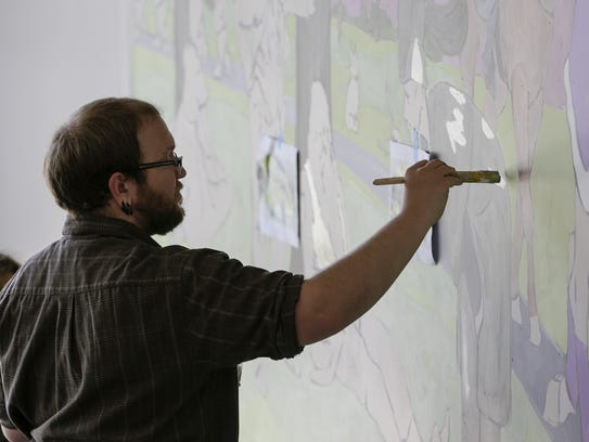 David Carpenter works on a new mural in the Manitowoc