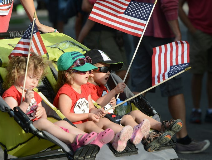 Children watch the community race at the 15th annual FireKracker 5K, hosted by the Fort Collins Running Club, at City Park on Friday.