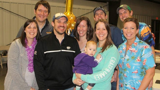 The Beach Party gang hold the first place symbol after winning the Ascension Lutheran Adult Trivia night fundraiser to raise money to pay for remodeling their recently donated building. Beach Party members are Andrew and Megan Piester, Aaron and Diane Traffas, Chris and Chelsea Boyd, Michael and Erica Edwards and 10-month-old Halle Edwards.