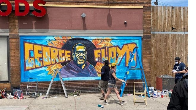 A photo by Daniel Wolpert of the mural for George Floyd created by a group of community artists on the side of grocery store Cup Foods in Minneapolis, just down the street from where Floyd was arrested and died. The artwork not only pays homage to Floyd, it has become a place to pay tribute to him.