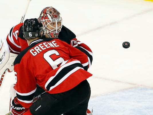 A shot by Philadelphia Flyers right wing Matt Read gets by New Jersey Devils goalie Cory Schneider, back, and defenseman Andy Greene before entering the net for a goal during overtime of an NHL hockey game, Friday, Dec. 4, 2015, in Newark, N.J. The Flyers won 4-3 in overtime. (AP Photo/Julio Cortez)