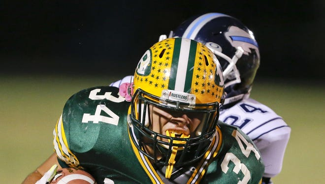 C.M. Russell's Andrew Grinde (34) is tackled by Great Falls High's Bostian Johnstone during a crosstown game at Memorial Stadium.