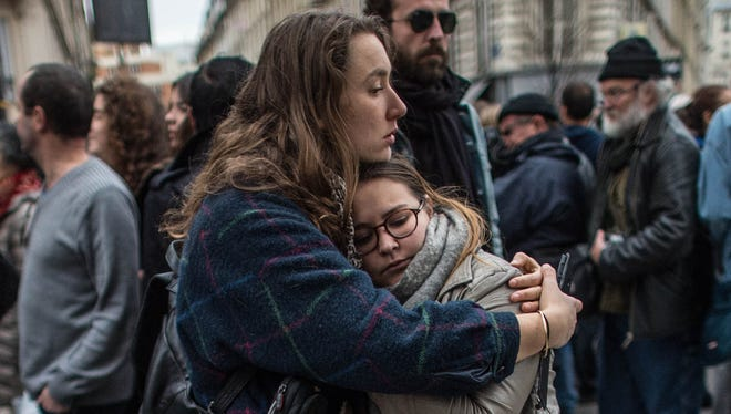 Two women embrace as they hold a board that reads 'Meme Pas Peur' (Not Afraid) in front of the Petit Cambodge restaurant, one of the Paris attack sites.