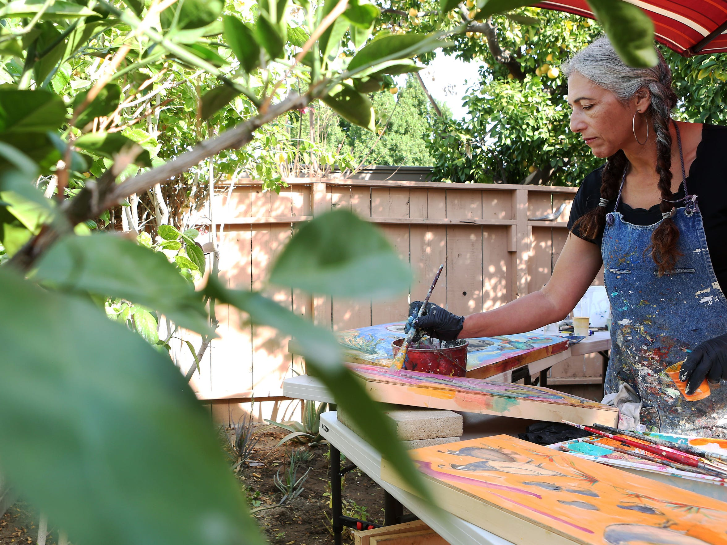 Painter Cristina Acosta paints a desert landscape in her backyard on Tuesday, January 20, 2015 in Palm Springs, Calif.