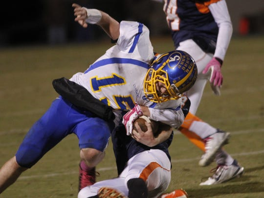 A Clarksville Academy quarterback is pulled down by