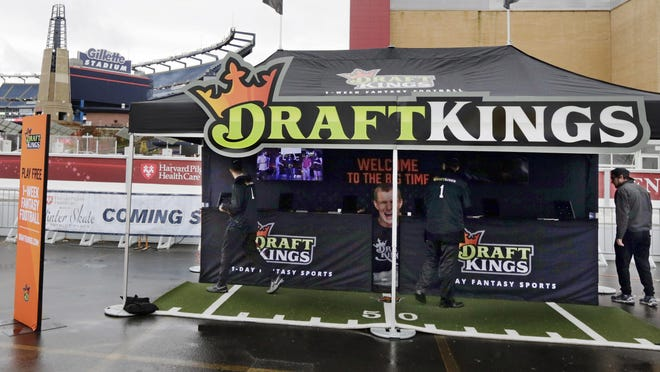 In this Oct. 25, 2015, photo, workers set up a DraftKings promotions tent in the parking lot of Gillette Stadium in Foxborough, Mass., before an NFL football game between the New England Patriots and New York Jets.