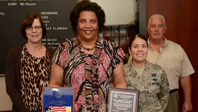 Carolyn Peeler, chief of manpower with the Military Personnel Flight at Holloman Air Force Base holds her two Roy Wilken Awards with members from her team inside the MPF building, Sept. 29. Peeler recently won this award for the second time since 2006. This award recognizes military and DOD civilians who exemplify the core values of their respective branch of service.