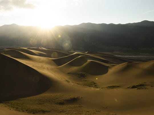 The sun begins to rise over the Great Sand Dunes National Park Saturday, June 27, 2015, near Alamosa, CO.