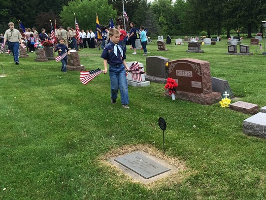 Cub and Boys Scouts placed flags on the graves of military