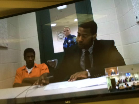Percy Sims, in orange jail jumpsuit, with attorney