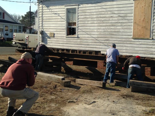 M. K. Miles, chairman of the Saxis Island Museum Board of Directors, photographs a crew working to lower the Crockett store on Saxis, Virginia, as they lower the building onto a new foundation on Friday, Dec. 11, 2015. The building is undergoing restoration and will become the museum's new home.