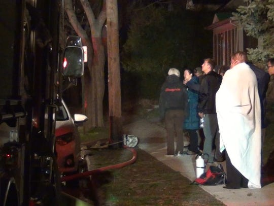 Bystanders gather across the street from a fire at