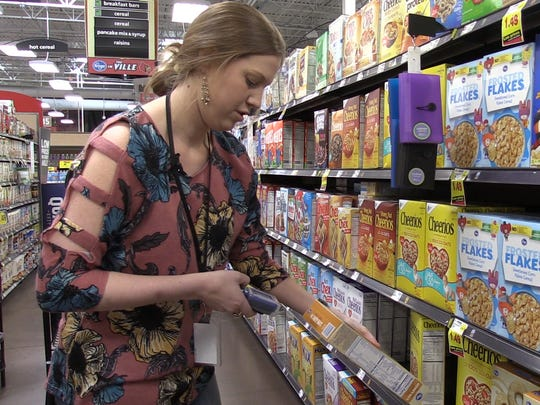 Reporter Maggie Menderski scans the barcode of a cereal box.