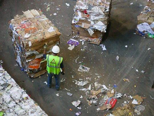 A worker picks at a bail of recycled cardboard before