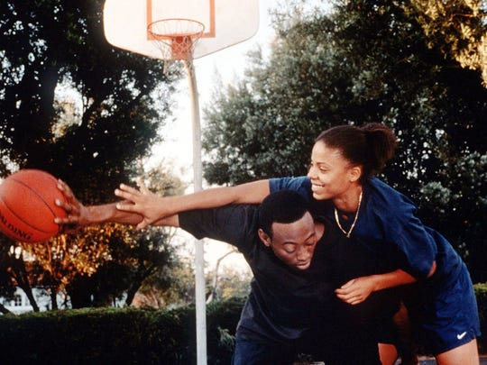 "Sanaa Lathan and Omar Epps play backyard basketball in this scene from ""Love & Basketball."""