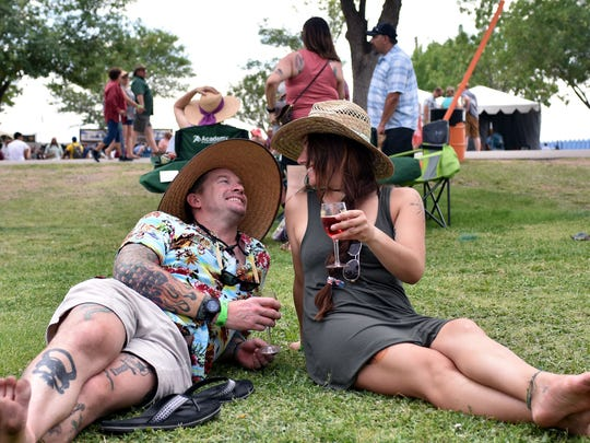 Randy Turner and Katherine Stewart from El Paso enjoy a glass of wine while sitting on the grass during the Las Cruces Wine Festival on Saturday, May 26, 2018.