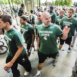 Members of the MSU offensive unit greet their fans as arrive at the Meet the Spartans event Tuesday August 13, 2013 at Spartan Stadium in East Lansing.  KEVIN W. FOWLER PHOTO