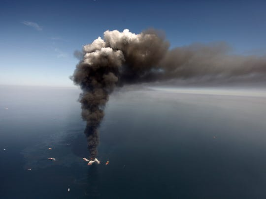 In this April 2010 file photo, oil can be seen in the Gulf of Mexico, more than 50 miles southeast of Venice on Louisiana's tip, as a large plume of smoke rises from fires on BP's Deepwater Horizon offshore oil rig. Deep-water drilling is set to resume near the site of the catastrophic BP PLC well blowout that killed 11 workers and caused the nation's largest offshore oil spill five years ago off the coast of Louisiana.