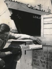 Sam Librizzi of Shorewood, a checker for Hansen Storage Co., places a Milwaukee sticker on a machine being shipped to Calcutta, India, by the Davis Machine Co. from the docks on Jones Island.  This photo was published in the Aug. 20, 1965, Milwaukee Sentinel.