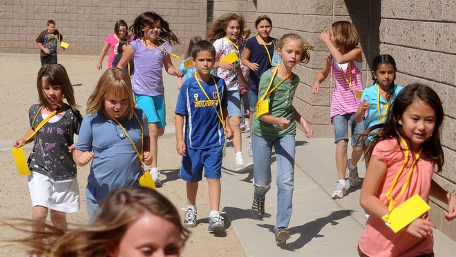 Kids at Brown Elementary School run the perimeter of the school yard during recess in 2010.