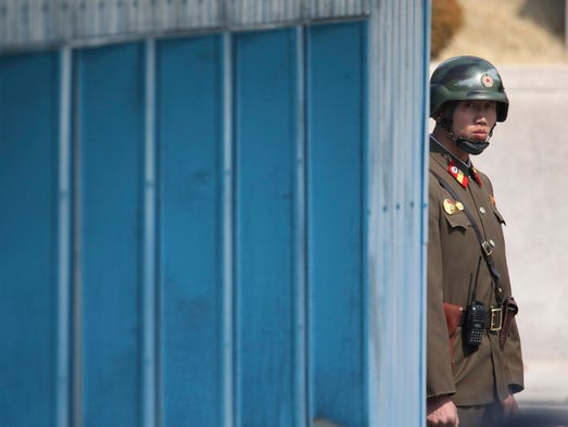 A North Korean soldier looks at the south side while
