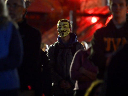A male wearing a mask listens to speakers during a