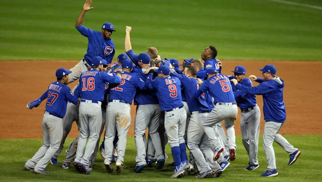 Chicago Cubs players celebrate after defeating the Cleveland Indians in Game 7 at Progressive Field.