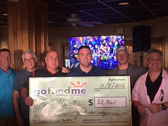 Marco Island Police Department officer Mark Haueter (center) receives a check for $28,366 to help with his medical bills. The money was raised through a GoFundMe campaign created by the MIPD.
