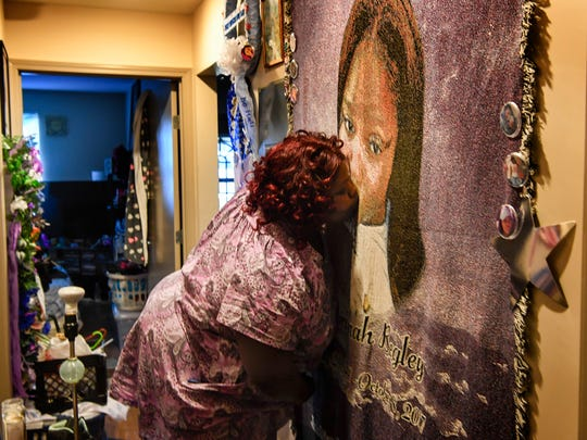Tika Begley kisses her daughters casket blanket that hangs in the hall on her new home in Nashville, Tenn., Monday, Nov. 27, 2017.