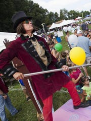 A costumed Willy Wonka hands out candy to young visitors