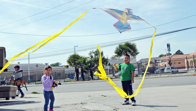 """Carlos Mejia, 6, and a friend maneuver his """"papalote,"""" or flying kite, under the power lines near Jesse Sanchez Elementary School in east Salinas."""