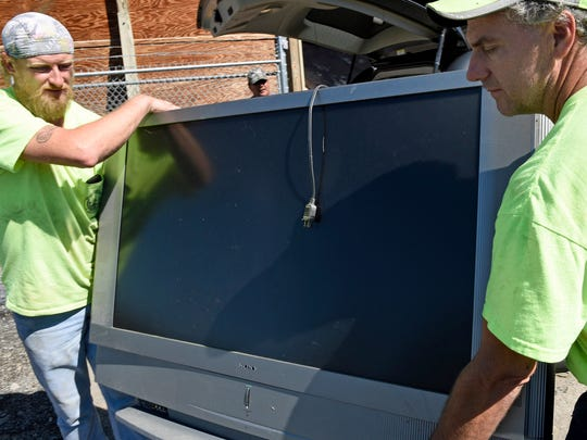 Ivan Mentzer, left, and Mark Holtry carry a discarded big screen TV during electronics drop off at the borough dump off Hollywell Avenue, Chambersburg on Tuesday, Sept. 27, 2016. Chambersburg residents were mailed two tickets to bring electronics to the dump for recycling. The event lasts through Saturday.