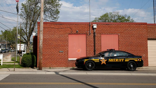 A Hamilton County sheriff's cruiser sits outside the Lincoln Heights municipal building Wednesday April 20, 2016. The village of Lincoln Heights owes the sheriff about $650,000 and told county officials last week it doesn't have enough money to cover that bill or to pay for future patrols.