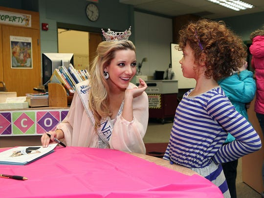 Miss New Jersey 2013, Cara McCollum, signs pictures at a book fair in South Jersey in 2014.