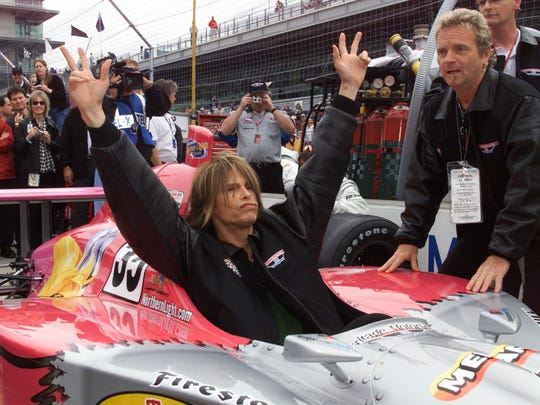 Aerosmith vocalist Steven Tyler waves while sitting in Jeff Ward's Aerosmith-sponsored car in 2001. Tyler's band mate, drummer Joey Kramer, is pictured at right.
