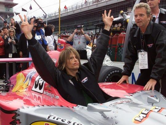 Aerosmith vocalist Steven Tyler waves while sitting