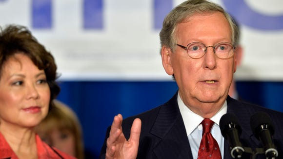 With his wife Elaine Chao, left, looking on, Kentucky Senator Mitch McConnell addresses his supporters following his victory in the republican primary, Tuesday, May 20, 2014, at the Mariott Louisville East in Louisville, Ky. (AP Photo/Timothy D. Easley)