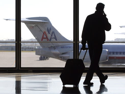 A traveler talks on his cellphone as he walks past a parked American Airlines at   O'Hare International Airport in Chicago.