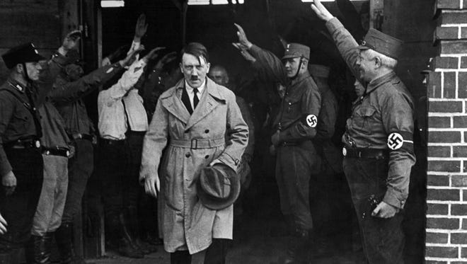 In this Dec. 5, 1931 file photo, Adolf Hitler, leader of the National Socialists, is saluted as he leaves the party's Munich headquarters.