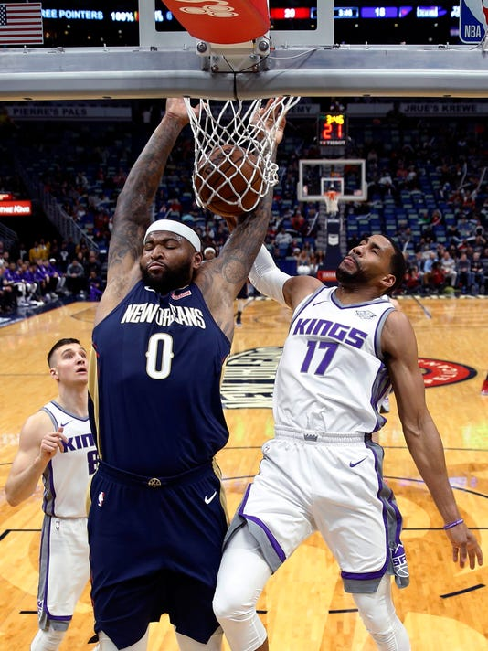 New Orleans Pelicans center DeMarcus Cousins (0) dunks and is fouled by Sacramento Kings guard Garrett Temple (17) during the first half of an NBA basketball game in New Orleans, Friday, Dec. 8, 2017. (AP Photo/Gerald Herbert)