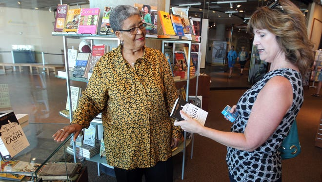 "April Agler (right) of Liberty Township, looks over a copy of ""Uncle Tom's Cabin,"" which she purchased at Smith & Hannon, the only black-owned bookstore in the city.  At left is Joyce C. Smith, who owns the store, which is located in the National Underground Railroad Freedom Center."